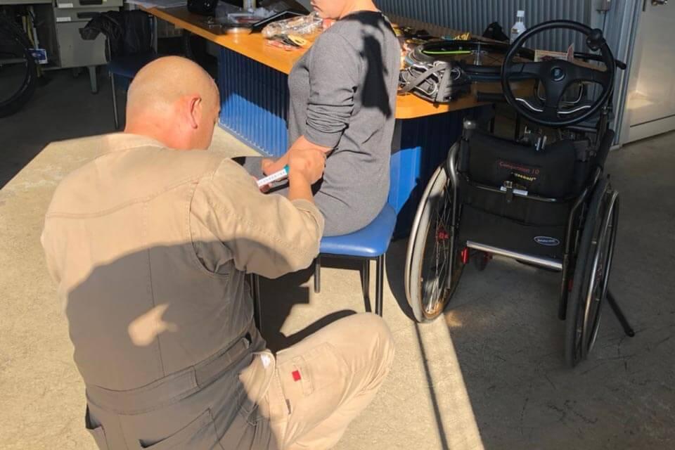 オーダーメイド車いすを製作するために、体を採寸しています。