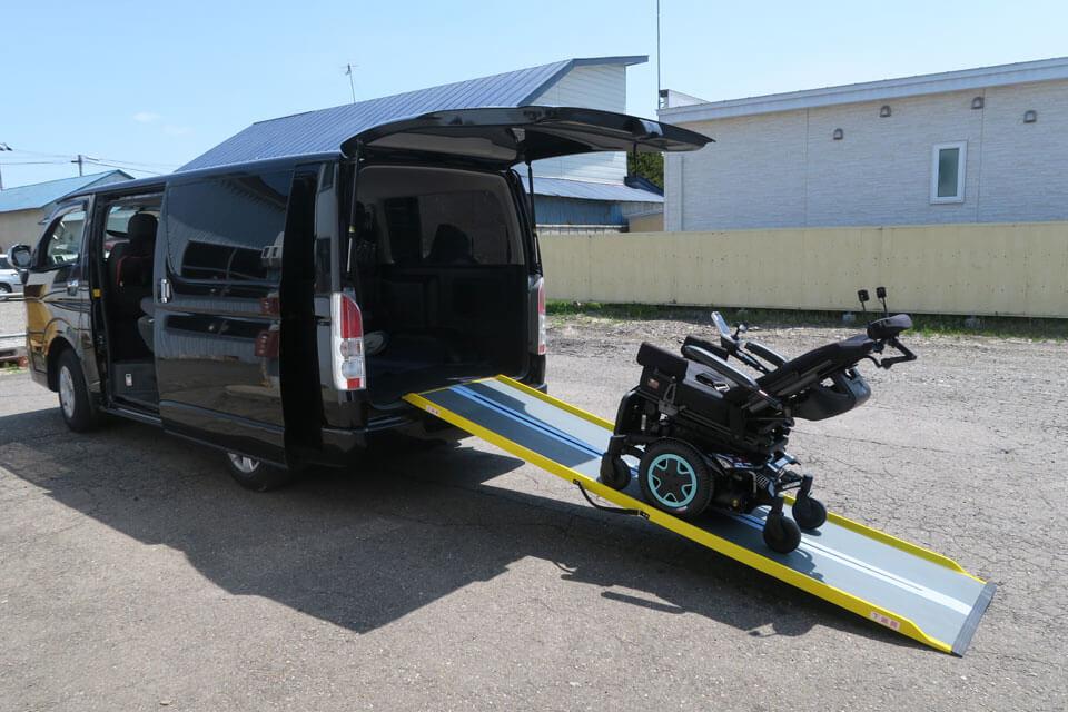 ハイエースにポータブルスロープを使って電動車いすを積み下ろししている写真